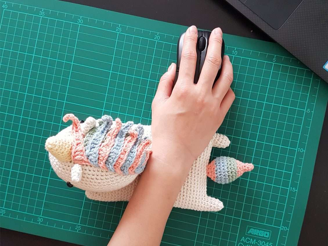 Hand on computer mouse with wrist resting on a crochet unicorn cushion.