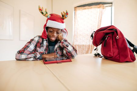 Teen Student With Digital Tablet Playing Online Christmas Word Search Games