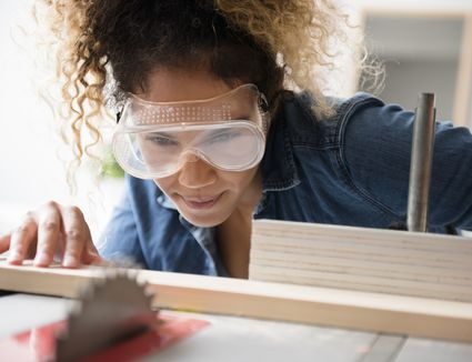 Woman wearing safety goggles while cutting wood