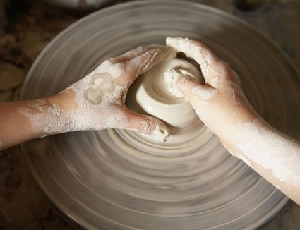 Sculpting clay on pottery wheel