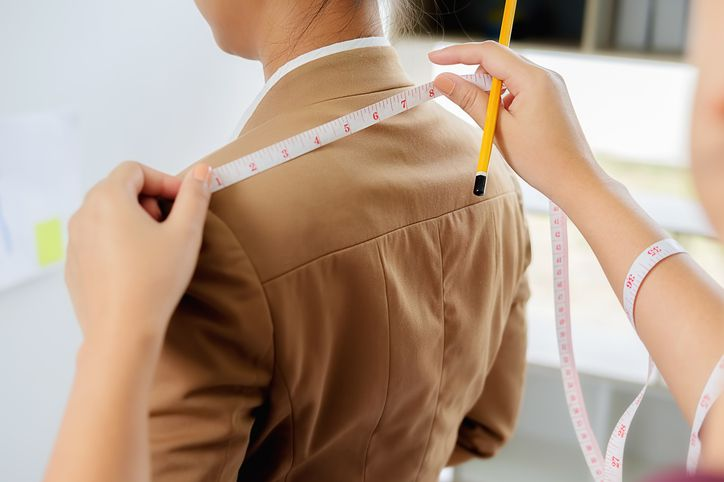 Tailor measuring woman's shoulder