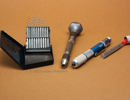 A set of miniature drills in a drill index, along with a revolving head pin vice and a mini drill.