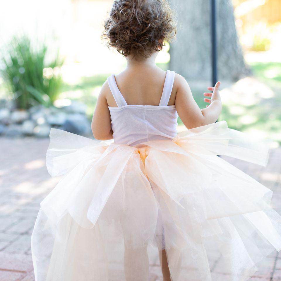 Child facing backwards in a tutu
