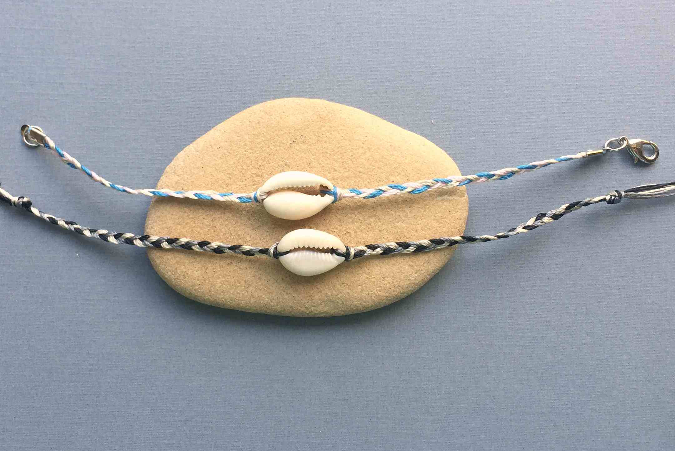 A pair of braided shell bracelets
