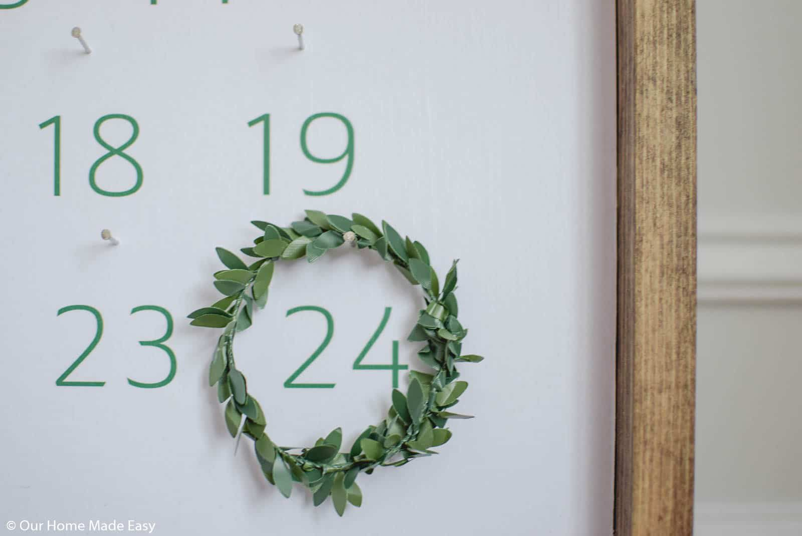 A wall art advent calendar in a wood frame with large green numbers.