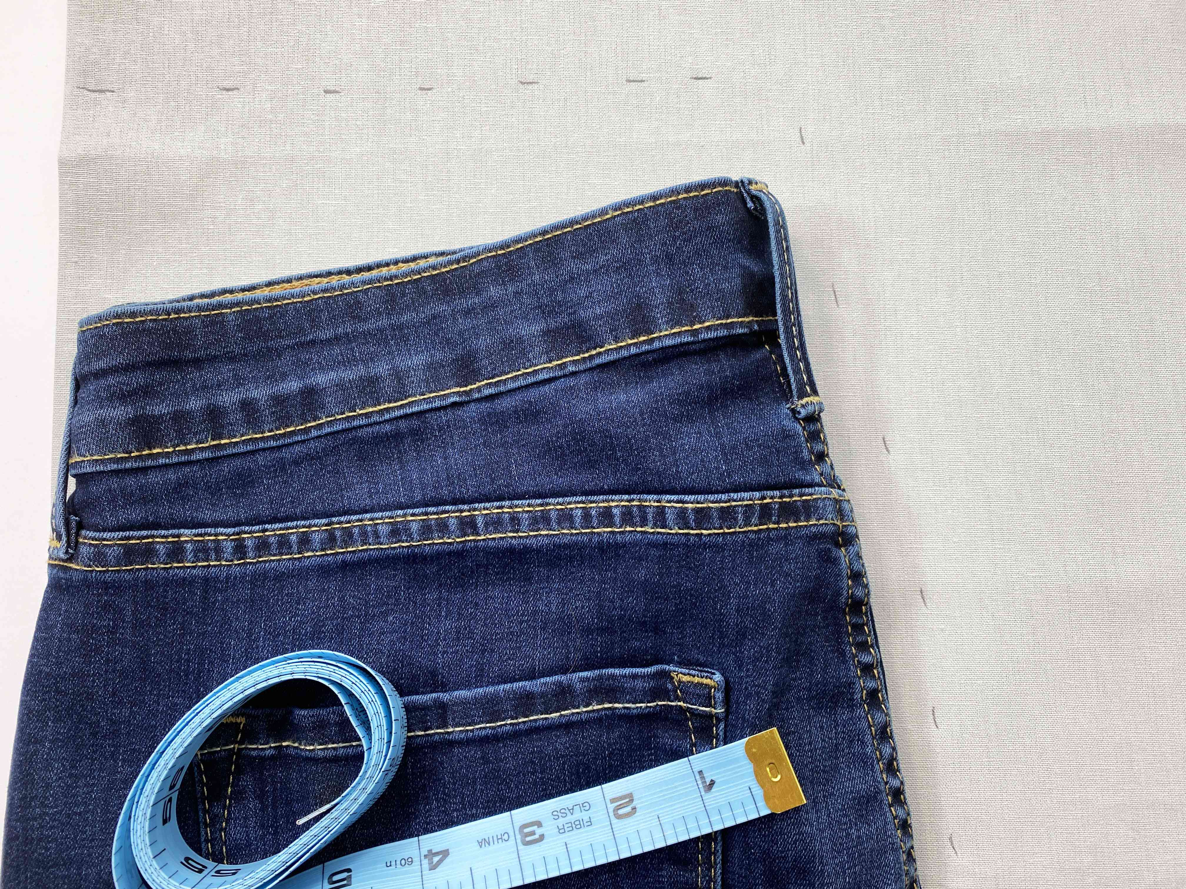 Jeans, tape measure, and fabric