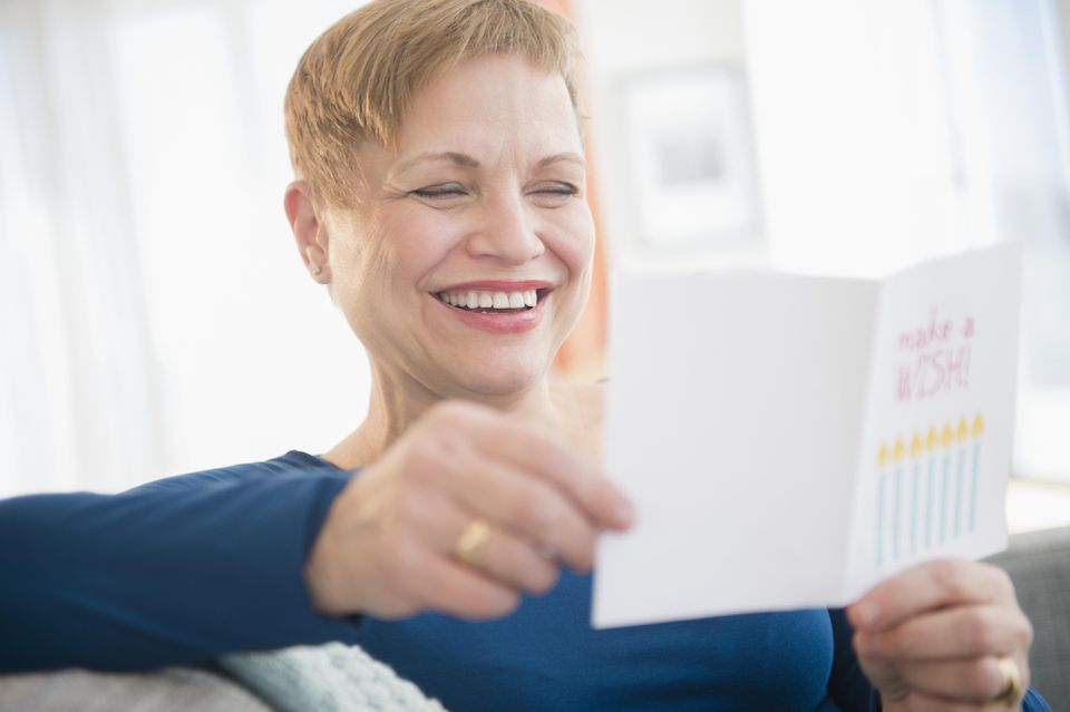 Caucasian woman reading birthday card