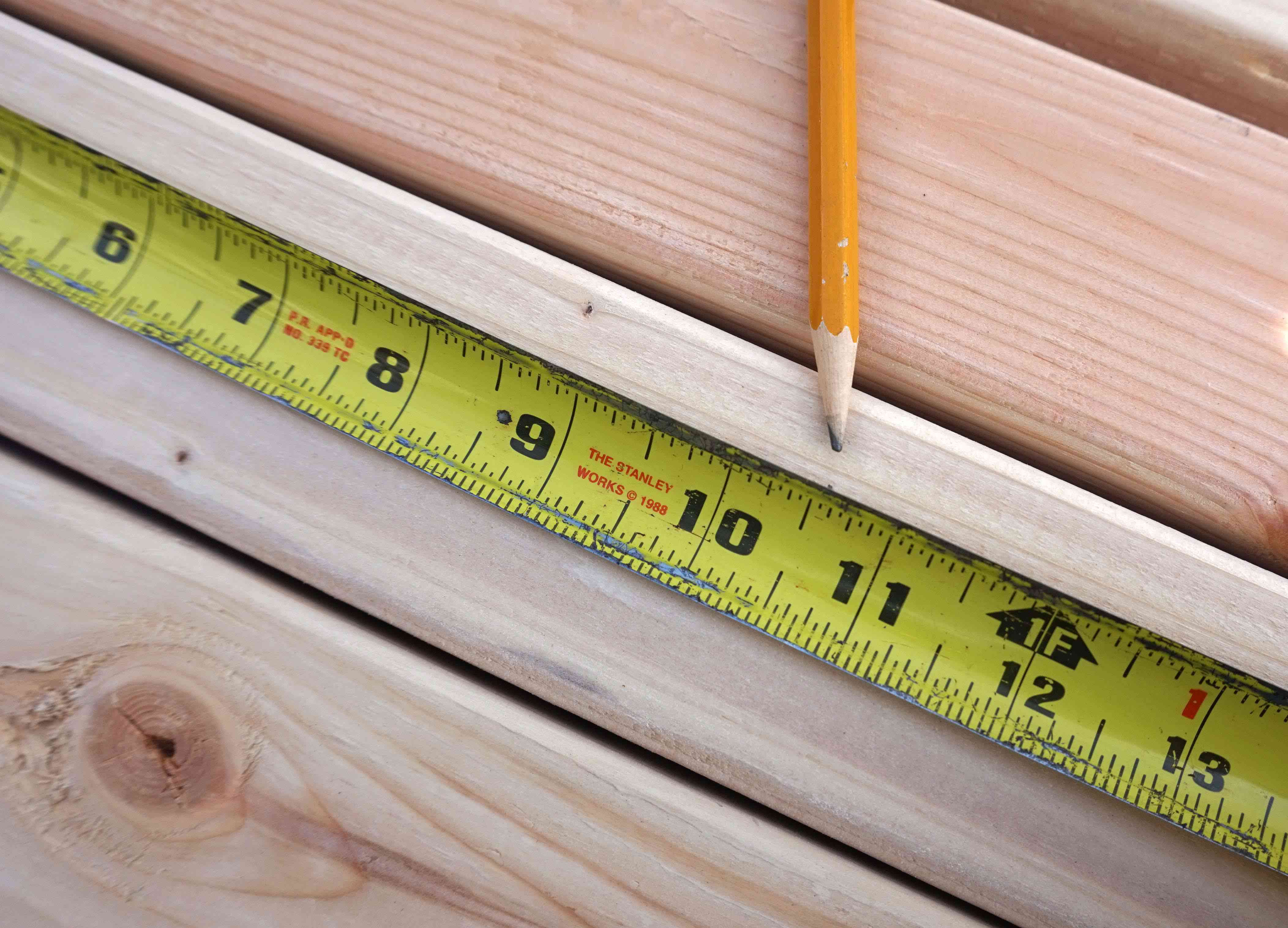 A pencil and measuring tape marking a wooden board