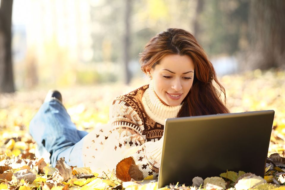 Satisfied young woman using computer in park.