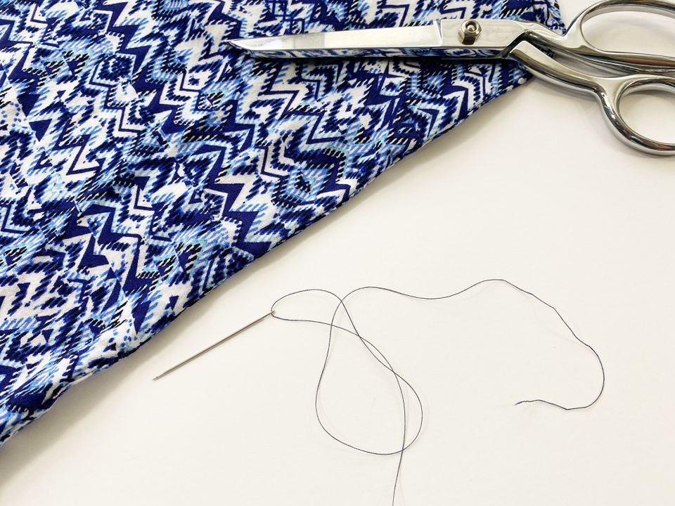 A blue blouse, scissors, and a threaded needle