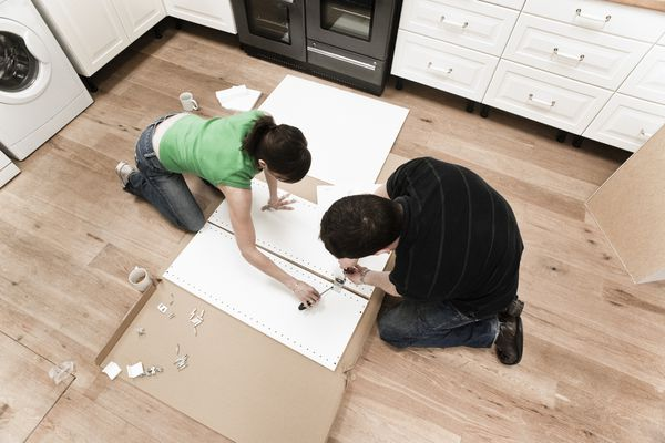 Man and woman building a kitchen cabinet