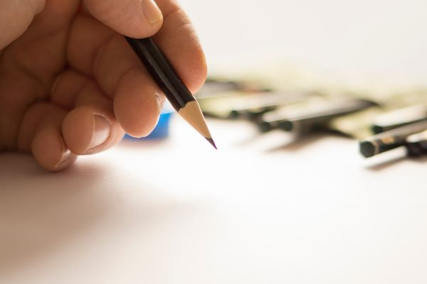 Close-Up Of Hand Holding Pencil
