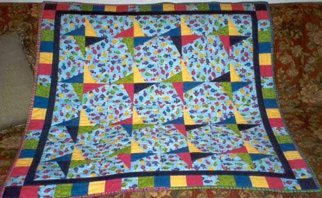 Baby quilt with pinwheel design draped over a couch.