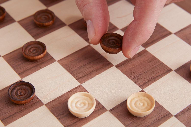 person moving a brown checker piece
