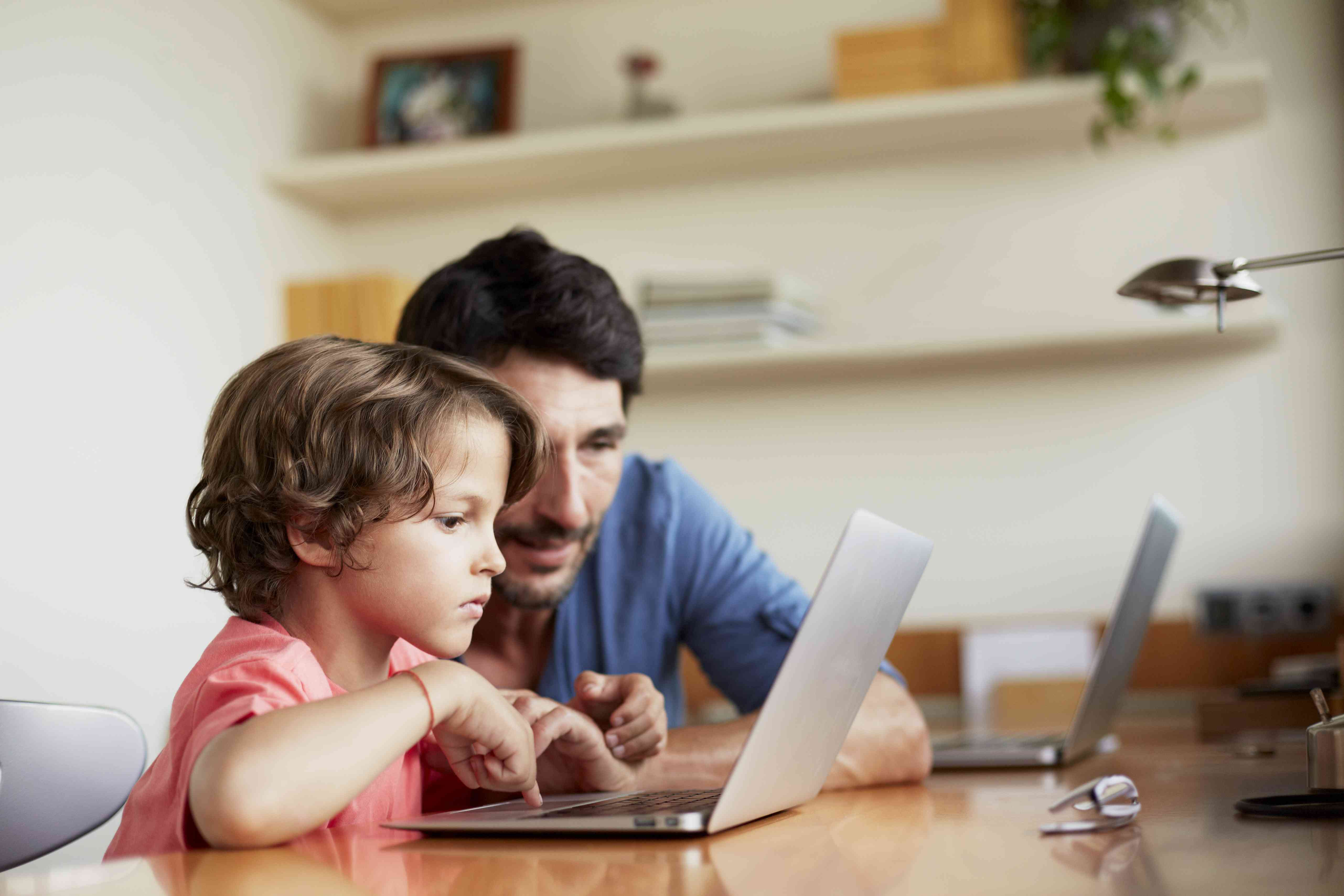 Man assisting son in using laptop
