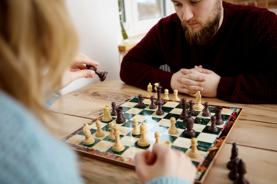 Man Playing Chess With Woman At Home