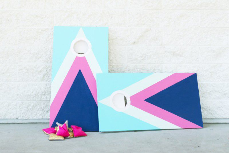 Two colorful wood cornhole boards and a pile of bean bags.