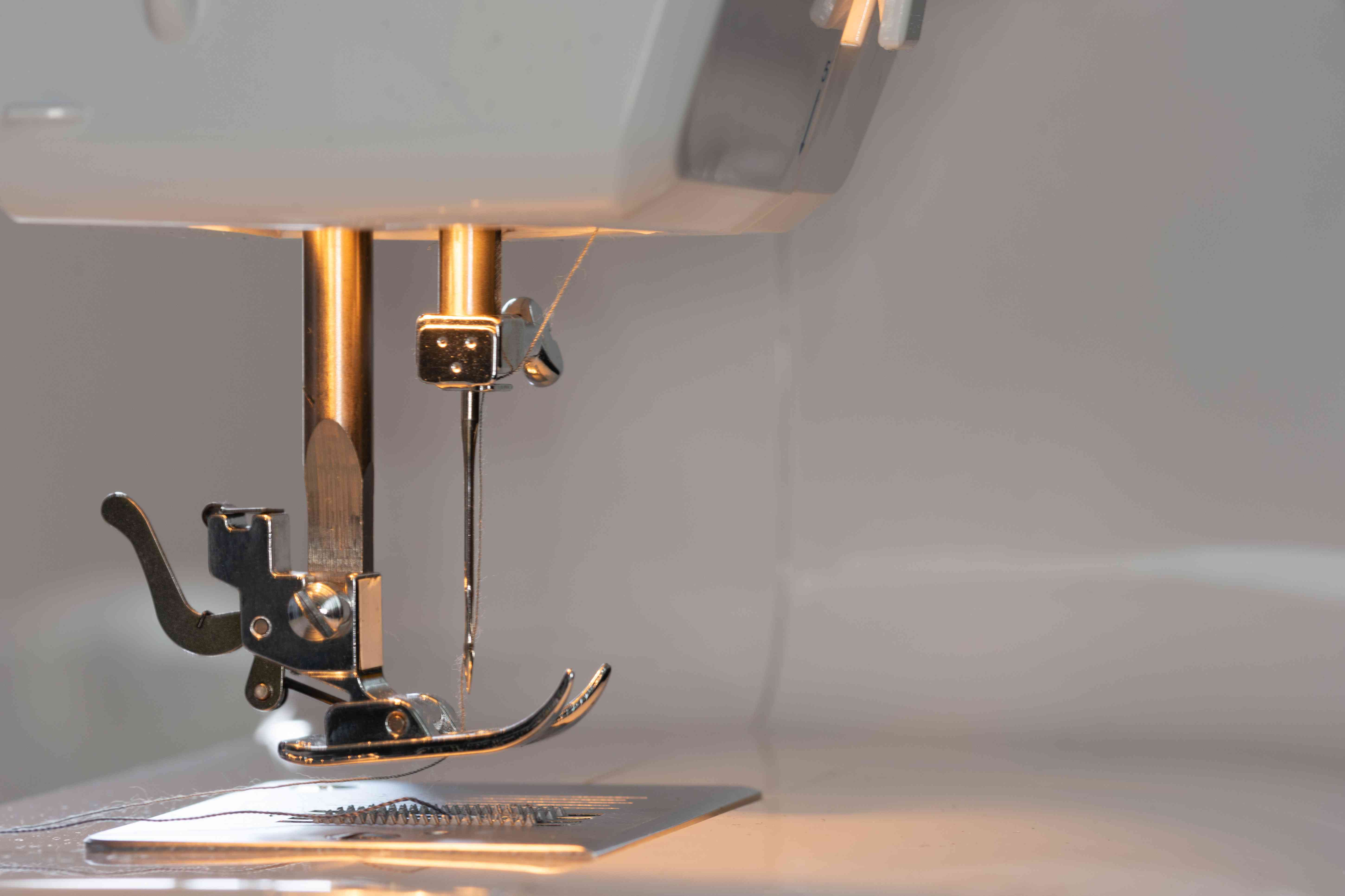 Detailed view of a sewing machine illuminated directly near the mechanics