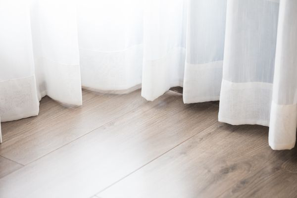 Close-Up Of White Curtain Over Hardwood Floor