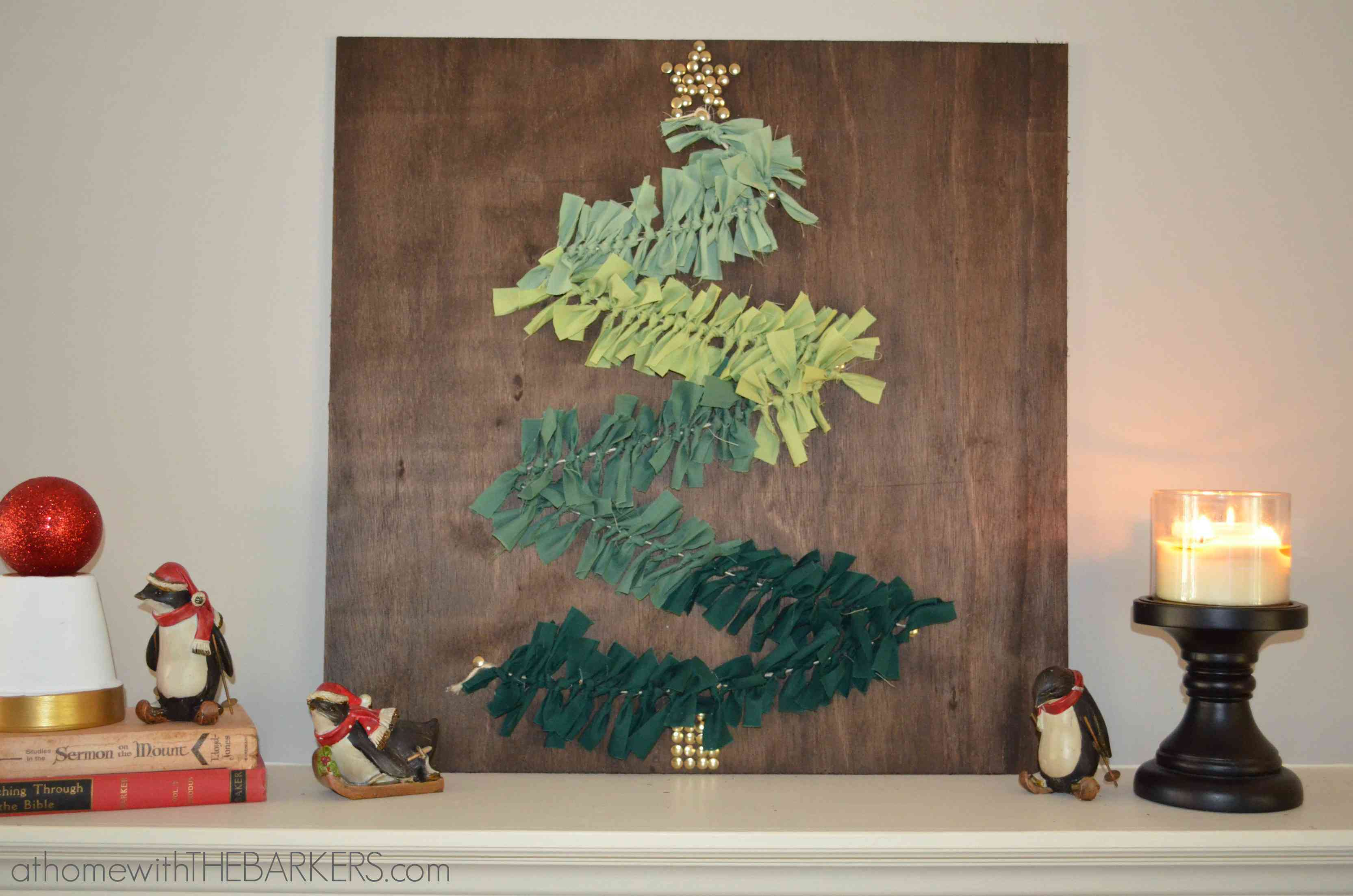 A piece of wood with green Christmas tree art on a mantle.