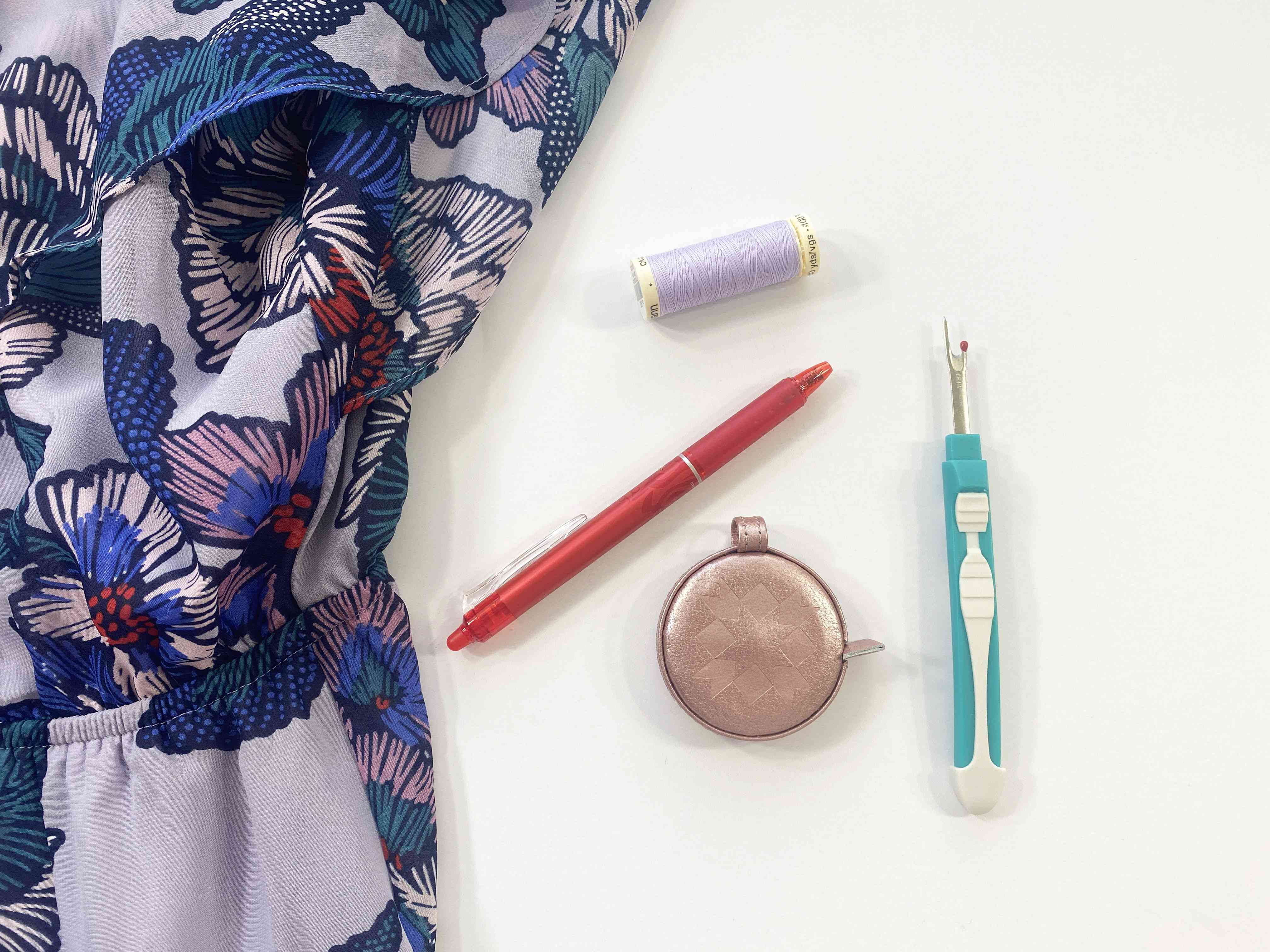 A dress, thread, pen, seam ripper, and measuring tape