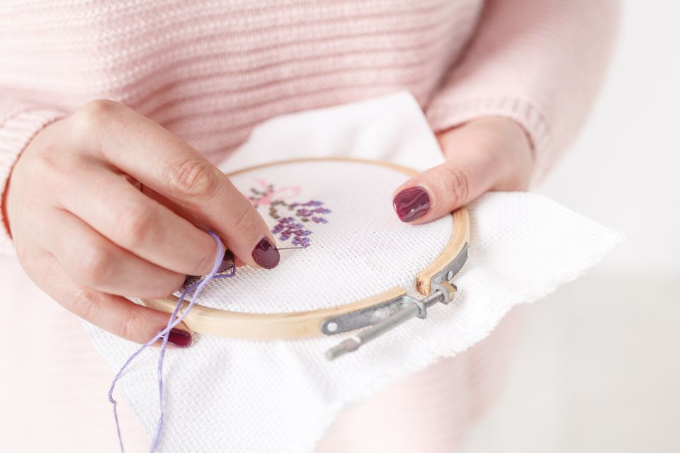 cross-stitched pillow in female hands