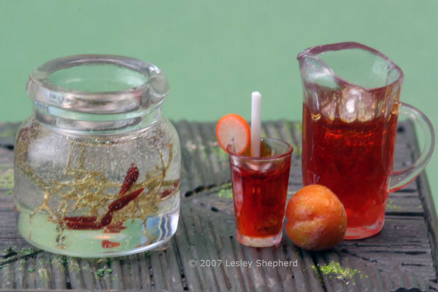 Miniature drinks and tadpoles in a jar made using epoxy resin.