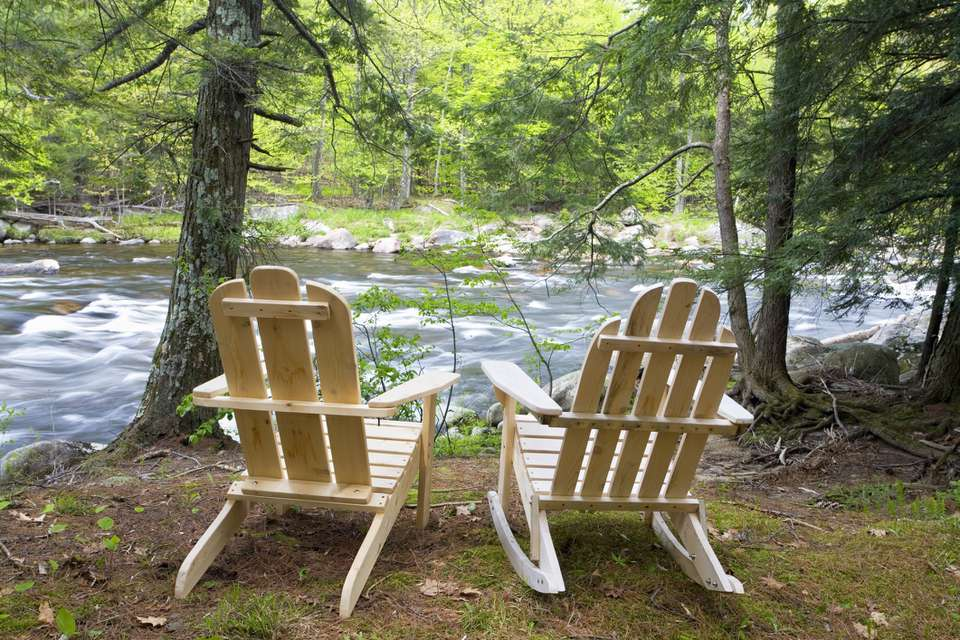 A pair of adirondack chairs by a mountain river in the Adirondack Mountains