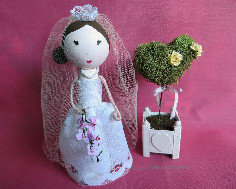 Clothespin bridal doll with lace and tulle veil and ribbon gown, next to a heart shaped topiary.