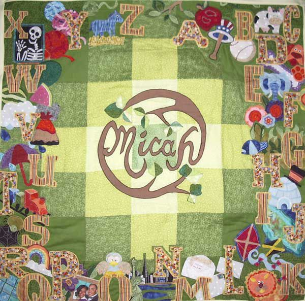 """Green and yellow baby quilt with the word """"Micah"""" in the middle adorned with letters of the alphabet."""