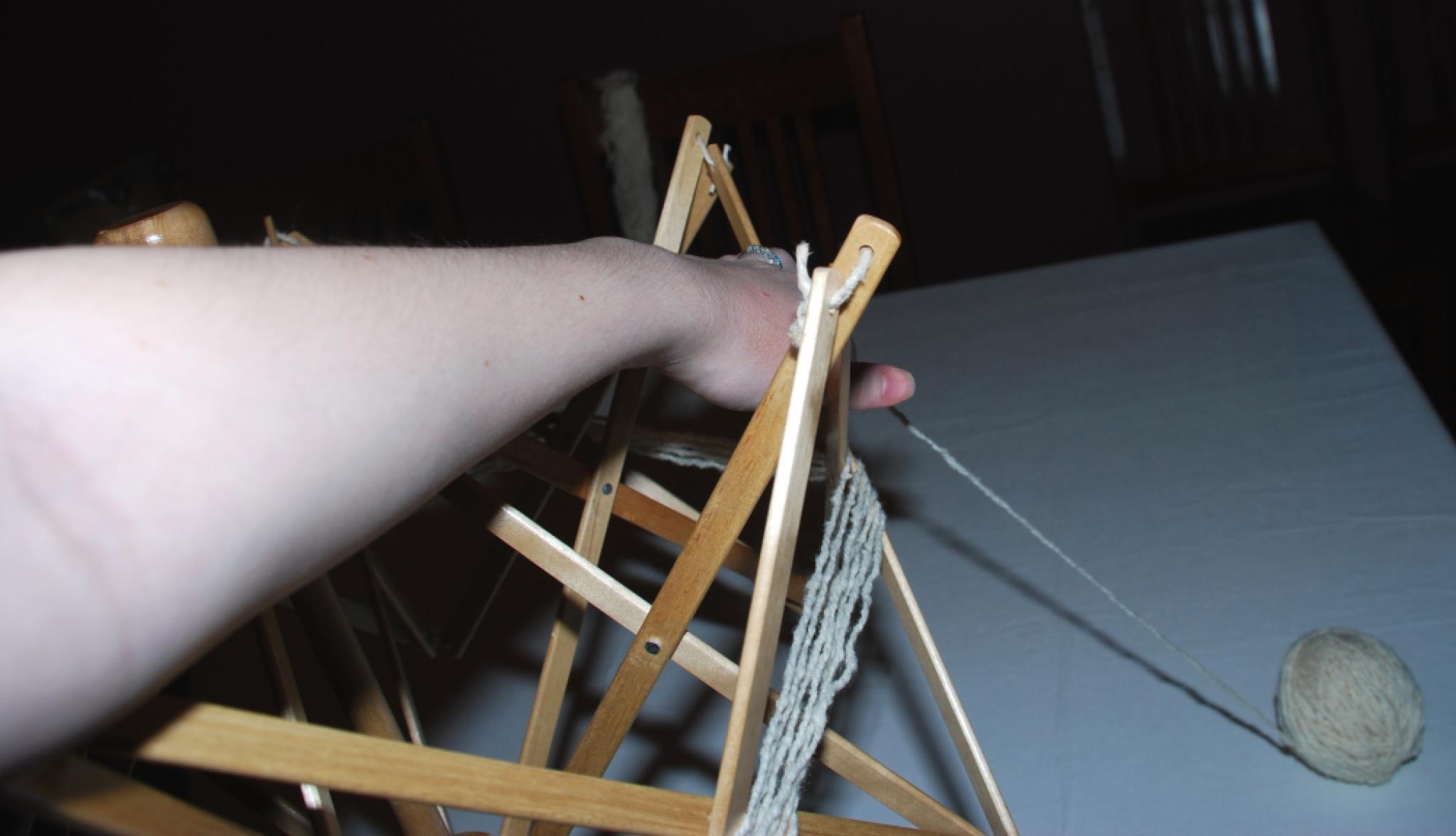 Person winding blue yarn over the yarn swifter.