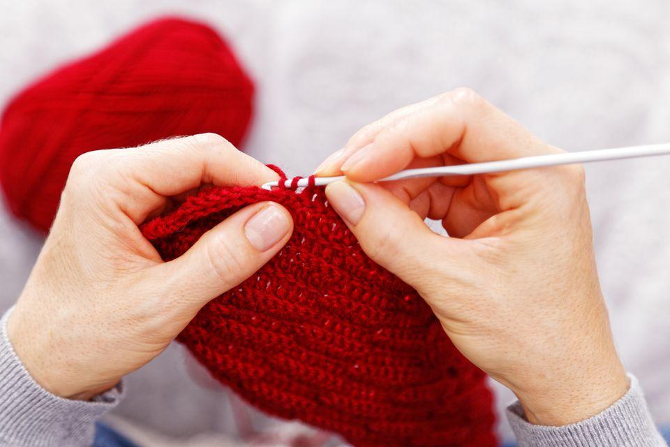 Closeup womans hands knitting red burgundy wool yarn