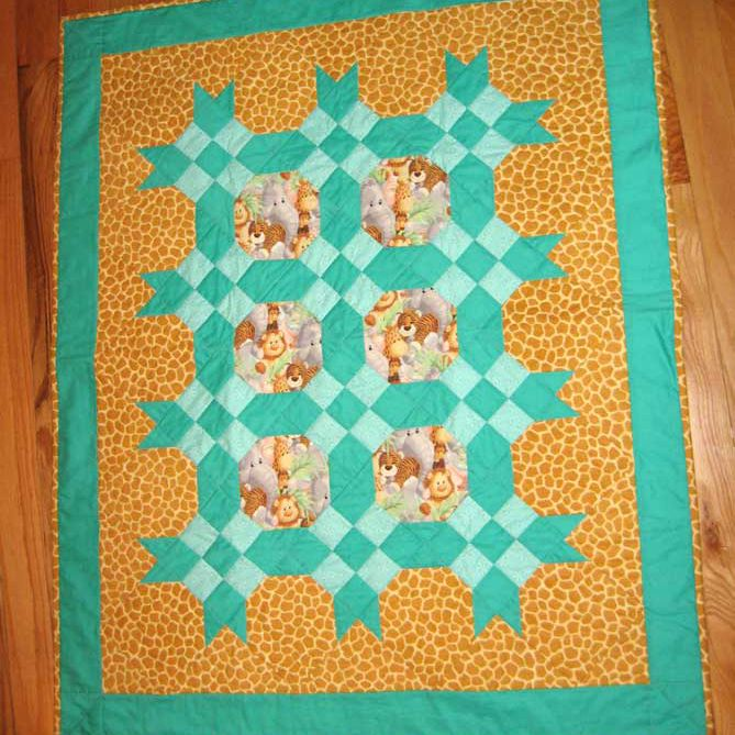Orange and teal jungle baby quilt lying on the floor.