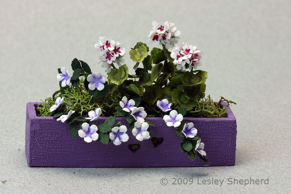 Dolls house plants fill the interior of a painted 1:12 scale window box with heart cutouts.