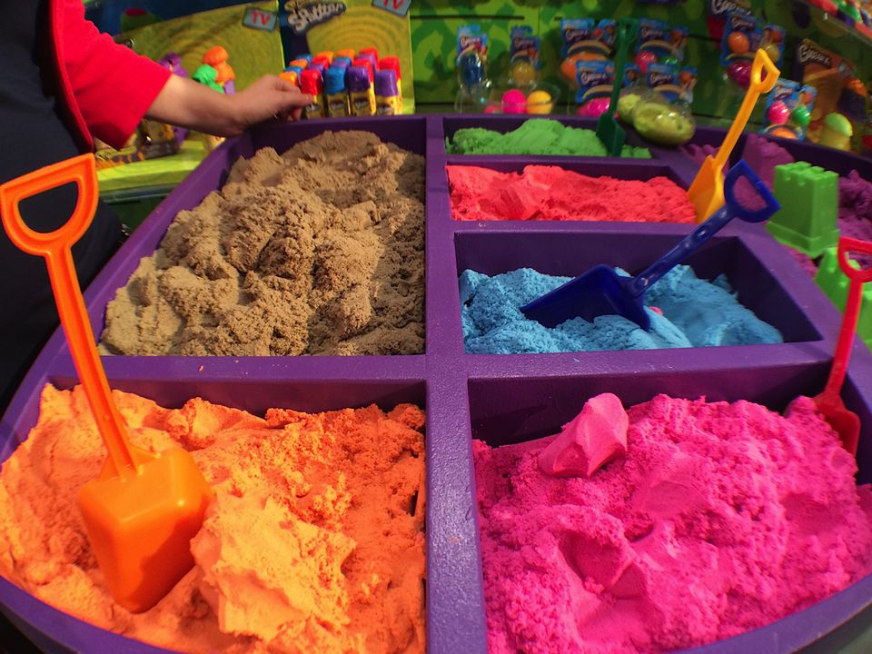 Kinetic Sand in brown, orange, pink, blue, and red colors with coordinating shovels.