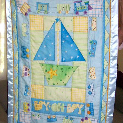 Person holding baby boy quilt with sailboat.