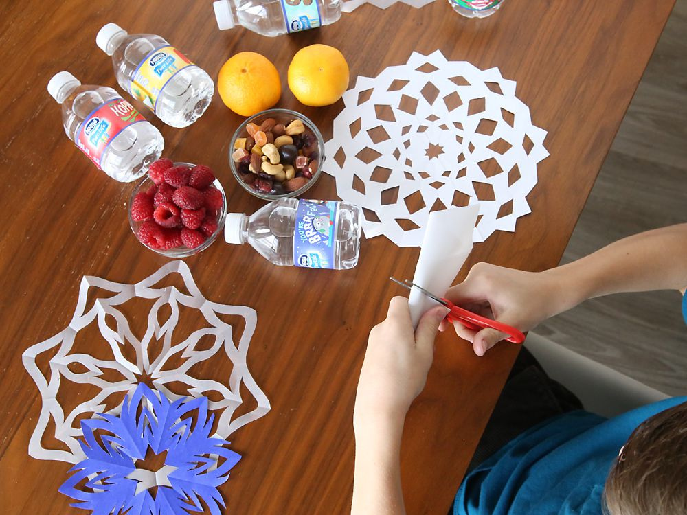 A boy using snowflake patterns to make paper snowflakes