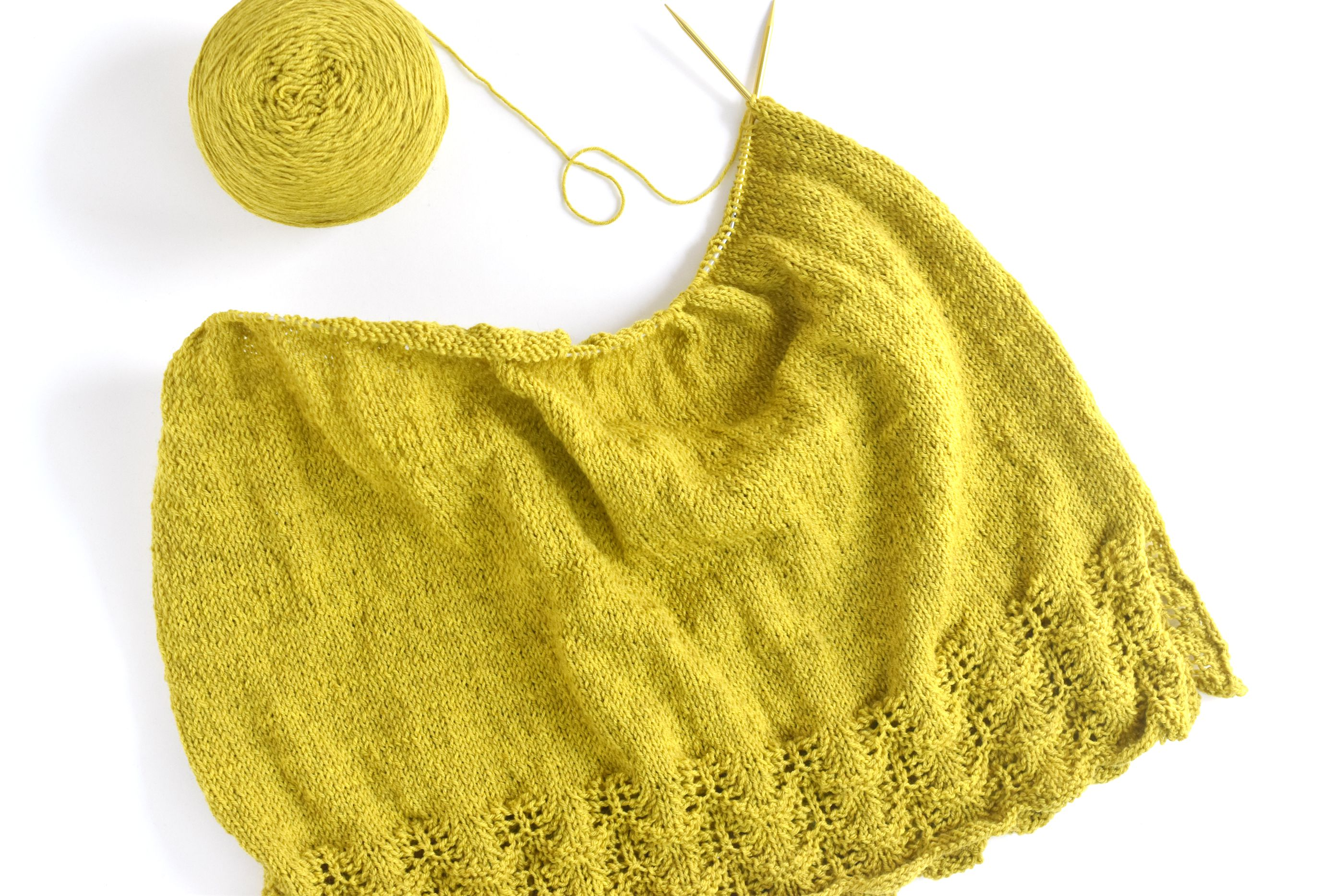 A ball of yarn and two needles next to a torso of a tunic