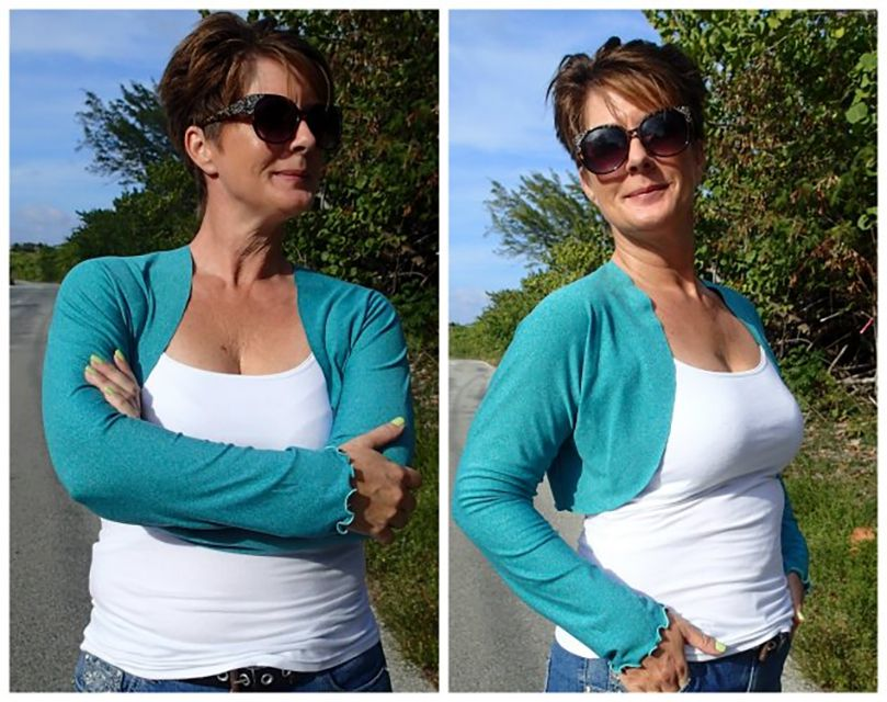 A woman wearing a teal shrug with a white shirt