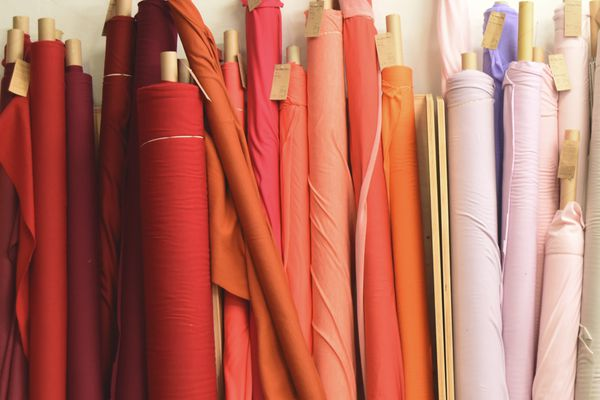 Stack Of Rolled Textile By Wall