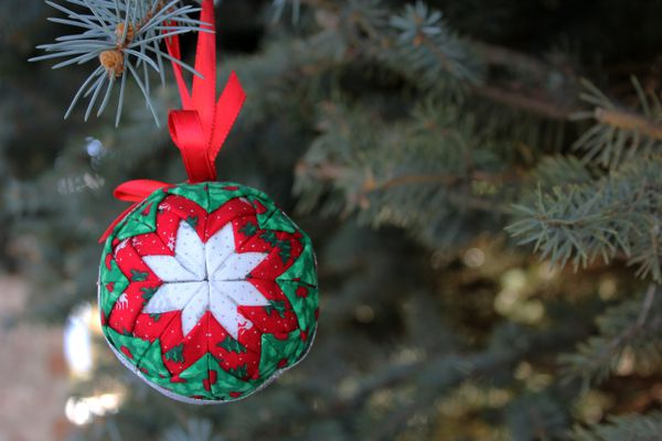 A quilted ornament hanging in a tree