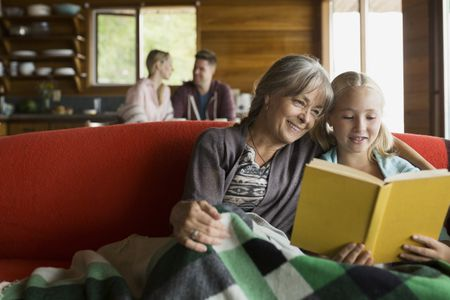 grandmother and granddaughter reading book on cabin sofa