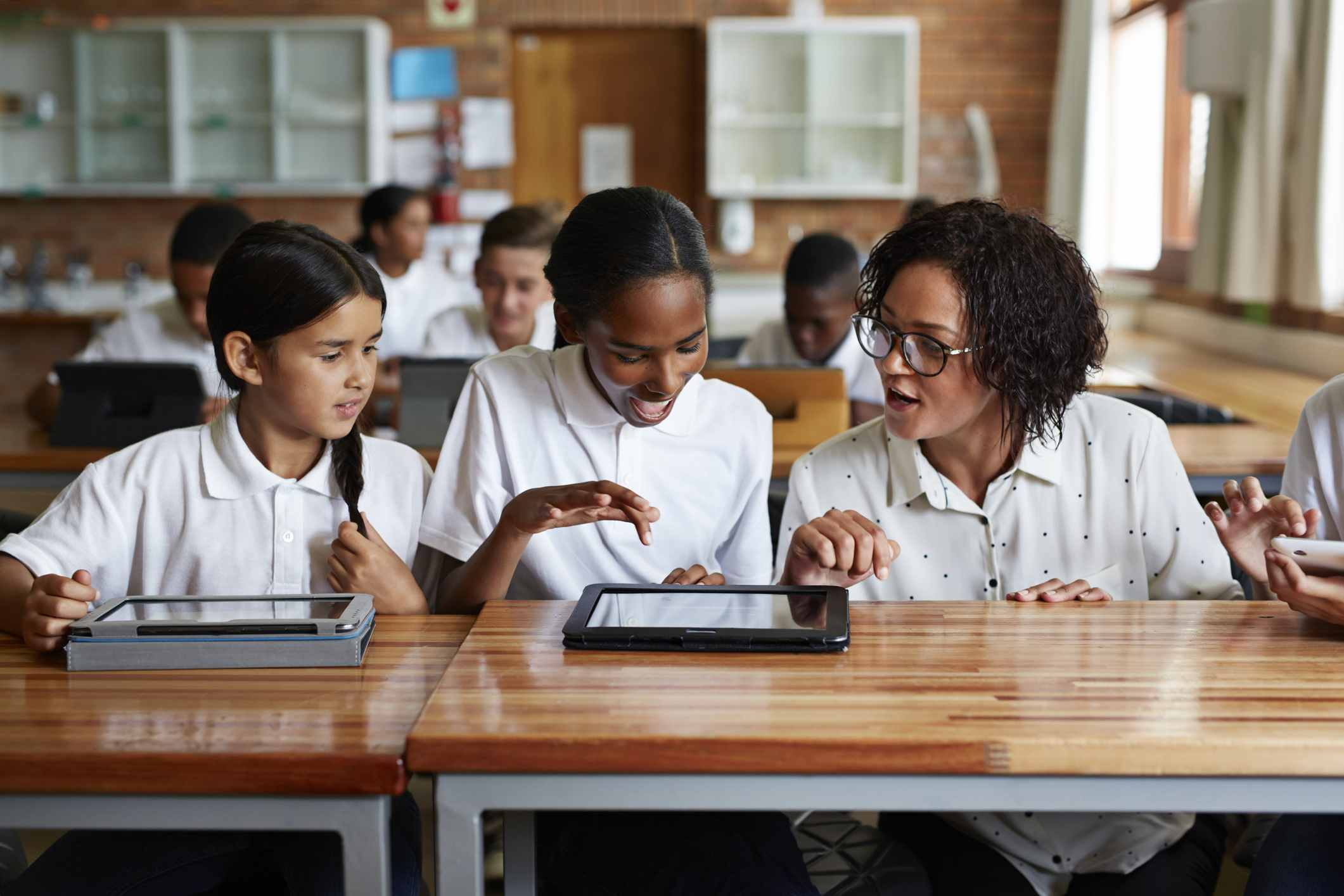Teacher assting students working with tablets