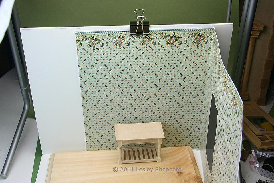 A piece of dolls house wallpaper is clamped to the back wall of a backdrop support for miniatures