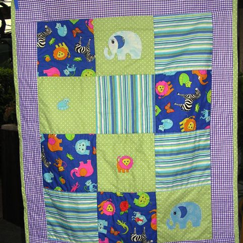 Baby quilt with elephants hanging from clothespins.