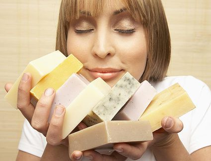 Young woman smelling assorted bars of soap, eyes closed, close-up