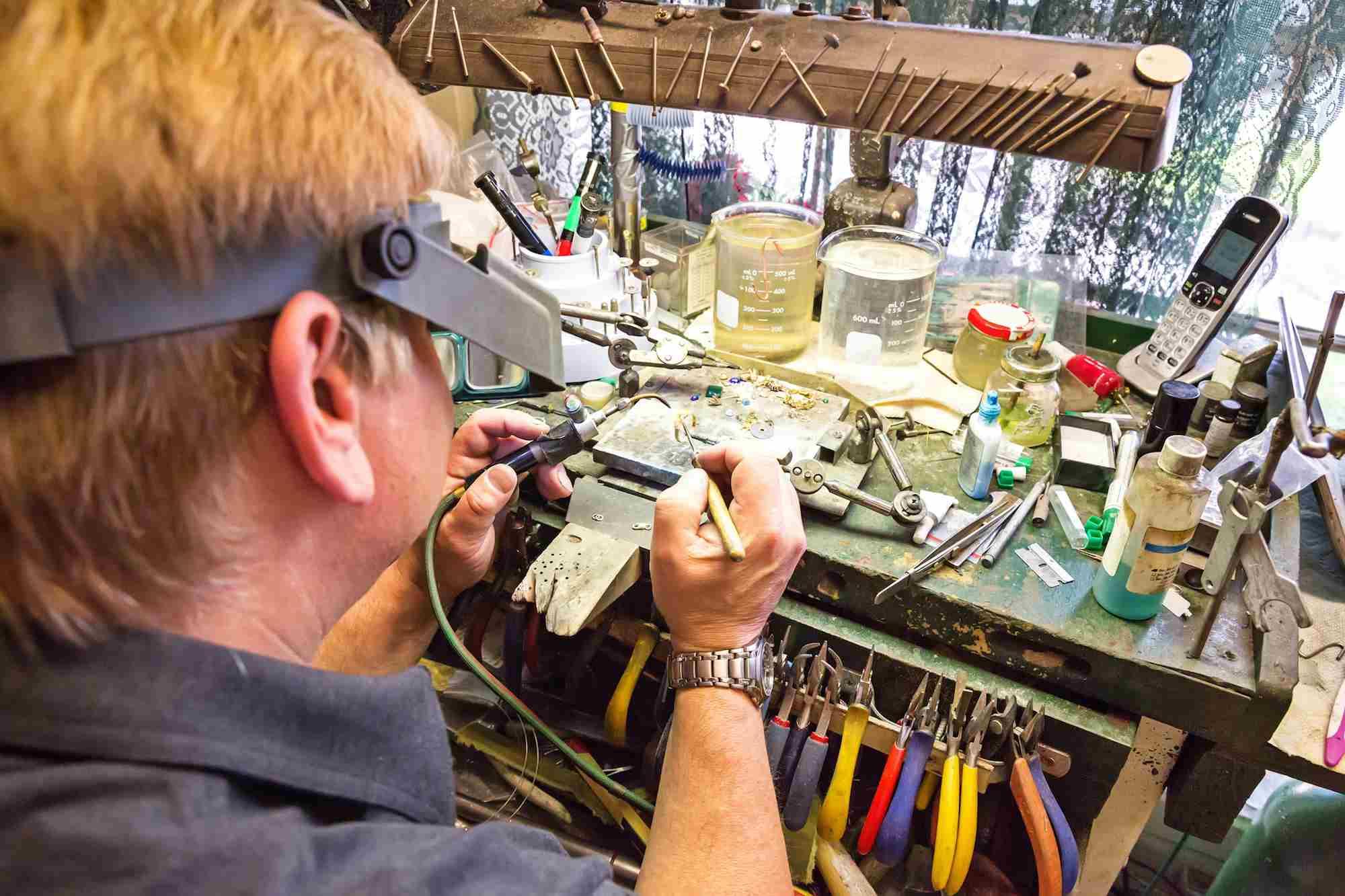 Jeweler at his workbench repairing a diamond ring