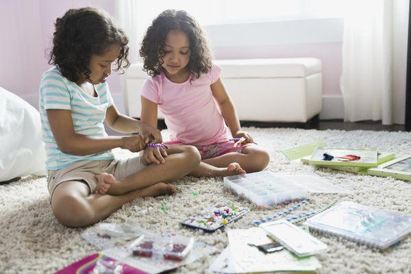 Little sisters making crafts together in bedroom