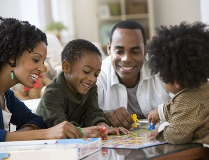 African American family playing board game together