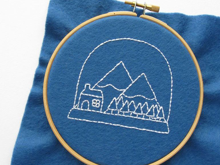 Embroidered winter snow globe on blue fabric in a hoop.
